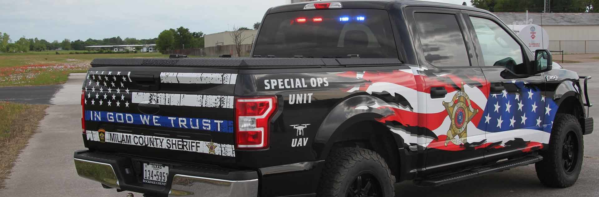 Black 4-door extended cab truck with red and blue lights in the back window. On the tail gate a black and white American flag, In God We Trust in white text, Milam County Sheriff in black text, Special Ops Unit in white text on the passenger side back top fender, and UAV with an outline of a drone in white text on the passenger side back bottom fender. On the passenger side back door is the Milam County Sheriff's Office badge. Across the front and back passenger side doors is a partial American Flag.